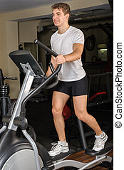 young man does workout at elliptical trainer in gym