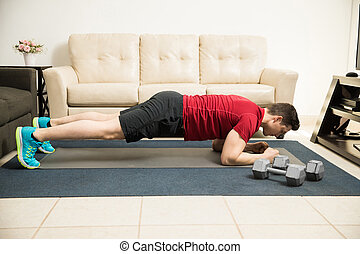 Young man doing a plank at home