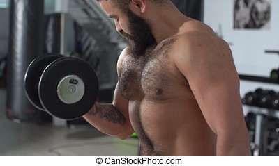 Young man doing an exercise on the biceps in the gym. athlete training with Dumbbells. slow motion