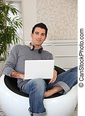 young man doing computer at home