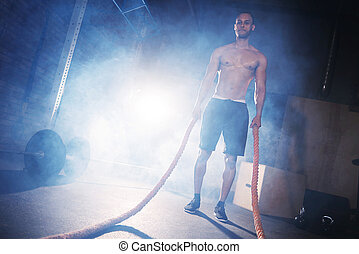 Young man doing crossfit training with ropes