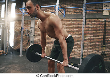 Young man doing deadlifts in fitness club