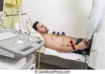 Young man doing EKG in hospital