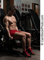 Young Man Doing Exercise For Biceps With Machine
