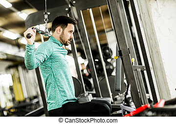 Young man doing exercise for triceps in the gym on mashine