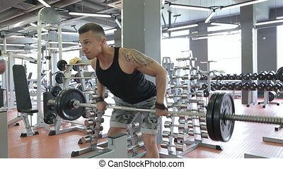 Young man doing exercises in a gym, workout