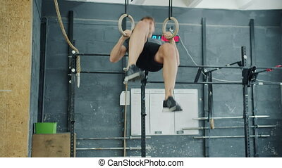 Young man doing exercises on still rings training in gym ...