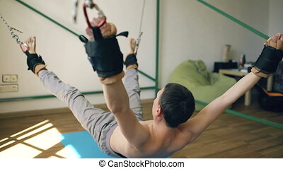 Young man doing exircise on quartering fitness equipment and...