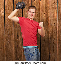 young man doing fitness with weights against a wooden wall