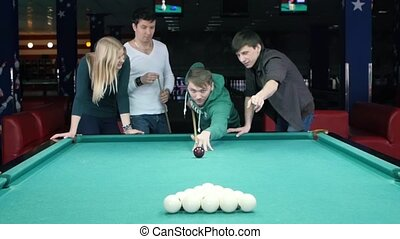Young man doing kick on a billiard ball. The company supports its friends. Slow motion