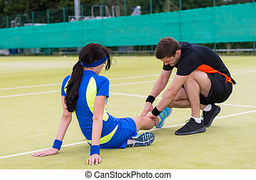 Young man doing massage to his female tennis partner