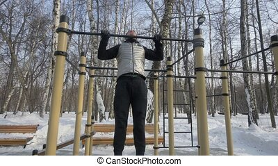 Young man doing pull up exercise on crossbar during winter...