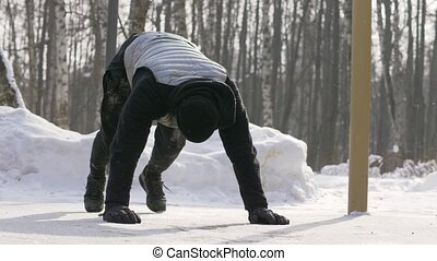 Young man doing push ups and stretching exercises on winter training outdoor