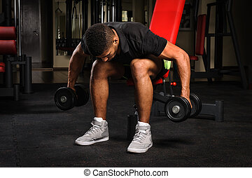 Young man doing Seated Bent Over Dumbbell Reverse Fly workout in gym