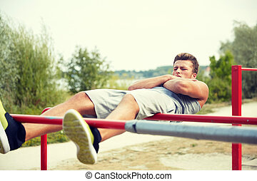 young man doing sit up on parallel bars outdoors - fitness, ...