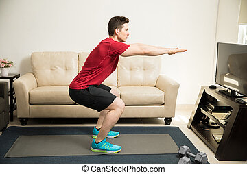 Young man doing squats at home