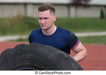 Young Man Doing Tire Workout Outdoor