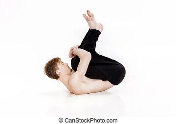 Young man doing yoga exercises. Studio shot on white background