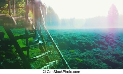 Young man down the stairs into the blue clear lake, slow...