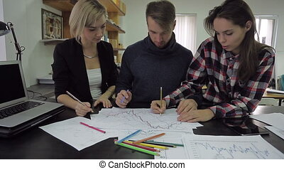 Young man draws a graph with colored pencils, explains something to the female colleagues and leaves