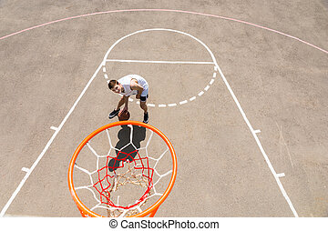 Young Man Dribbling Basketball Below Net on Court