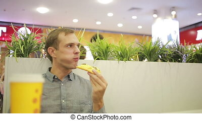 Young man drinking a coffee at the cafe. eating pizza