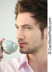 Young man drinking a cup of espresso