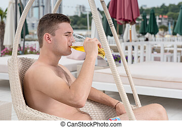 Young man drinking a glass of beer at the seaside
