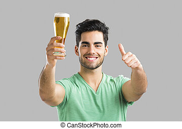 Portrait of handsome young man tasting a draft beer, isolated on gray background