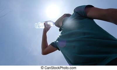 Young man drinking bottle of water standing outdoor in hot...