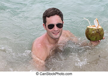 young man drinking coconut in water - young man drinking...