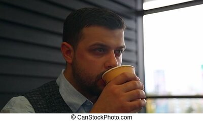 young man drinking coffee from disposable paper cup and looks into the distance. close-up