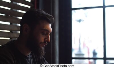 Young man drinking coffee next to the window in the cafe. A man with a beard
