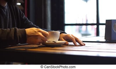 Young man drinking coffee next to the window in the cafe. A man with a beard.