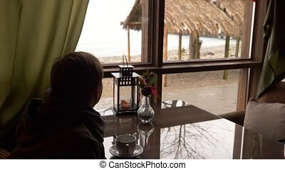 Young man drinking tea in cafe near window with sea view. a...