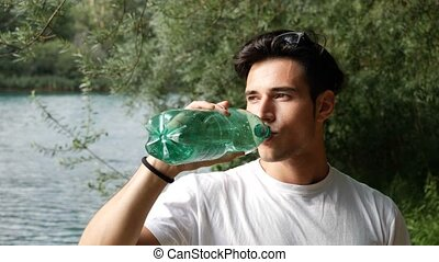 Young man drinking water from plastic bottle