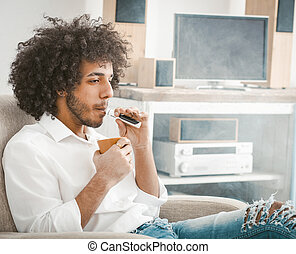Young man drinks coffee smoking of electronic cigarette sitting at home interior against the background of TV and sound system. Rest concept. Tinted image.