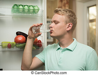 young man drinks water in the kitchen, standing at the fridge