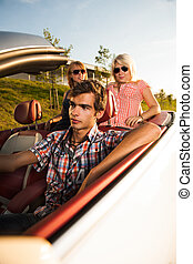 young man drives with two girls