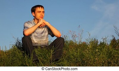 young man easy sits on grass and deeply breathes in park in summer