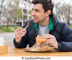 man eating a burger with fried potatoes in street food cafe