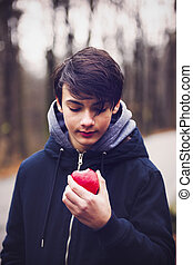 young man eating a red apple in the park