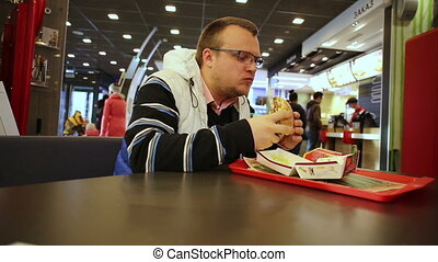 Young man eating burger in a fast food restaurant - Man...