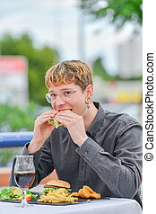 Young man eating burger in street restaurant