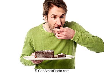 Young man eating chocolate cake