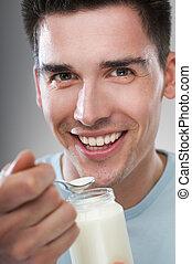 yogurt - young man eating yogurt close up shoot