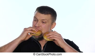 Young man eats a cheeseburgers. White. Slow motion