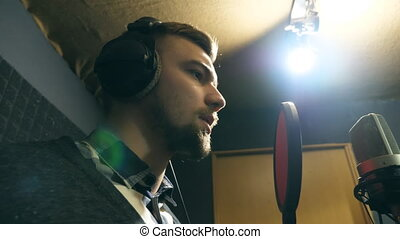 Young man emotionally recording new melody or song. Male singer in headphones singing song into the microphone at sound studio. Working of creative musician. Show business concept. Slow motion
