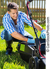 young man emptying lawnmower grass catcher after mowing the ...