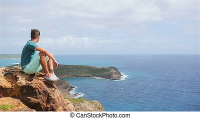 Young man enjoying breathtaking views from Shirley Heights...